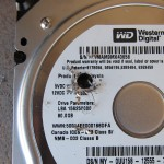 Hard drives contain many round platters inside that store the data. Drill through them.